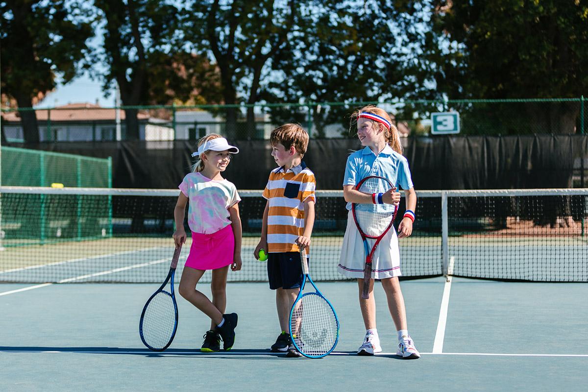 Trening tenisa dla dzieci. Dziewczynki i chłopiec na korcie tenisowym.