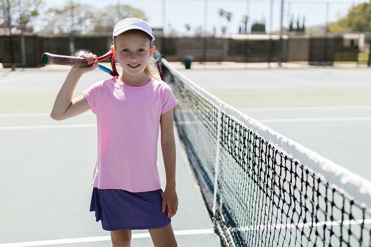 Trening tenisa dla dziewczyn. Dziewczynka z rakietą tenisową. W tle widać kort tenisowy w Krakowie.